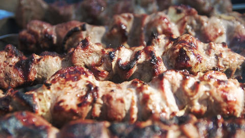 Macro of cooked kebabs smoking on skewers. Macro of barbecue meat on brazier Live Action