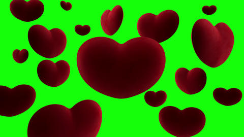 Red velvet hearts hang in the air around one large heart on a green background. Video loop Animation