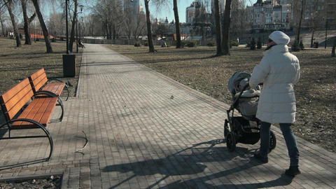 Happy mother passing with baby carriage. Relaxed girl walking with toddler boy Live Action