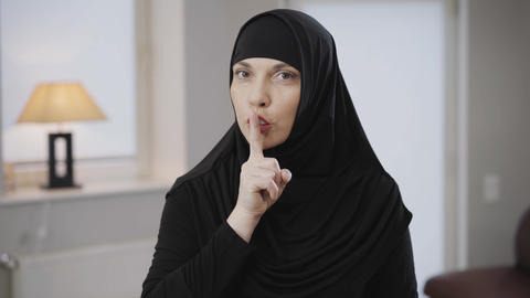 Middle shot of attractive Muslim woman in black traditional clothes looking at Live Action