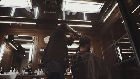 The client receives a haircut in a barbershop. Men's Hair Care Live Action
