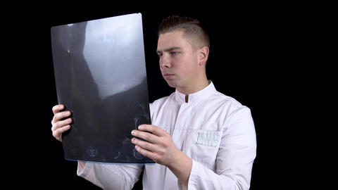 A young man doctor checks the results of an MRI scan of a spine. A man examines Live Action