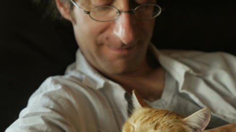 A man gently pets his orange cat while holding it in his arms in slow motion Footage
