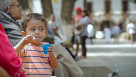PATZCUARO, MEXICO - CIRCA AUGUST 2016 - a child enjoys his ice cream with his fa Footage