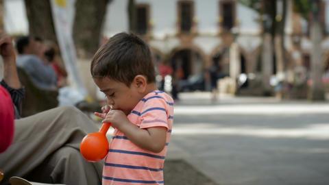 PATZCUARO, MEXICO - CIRCA AUGUST 2016 - a young boy tries to blow up a balloon i Footage
