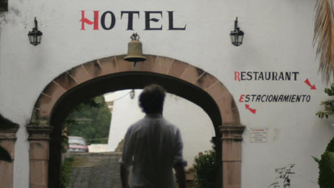 Silhouette of a man walking away from the camera through an arch at a colonial a Footage