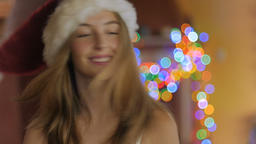 An attractive young woman wearing a santa hat in front of christmas lights Footage