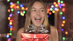 A gorgeous young woman holds out a gift while confetti falls down on her in slow Footage