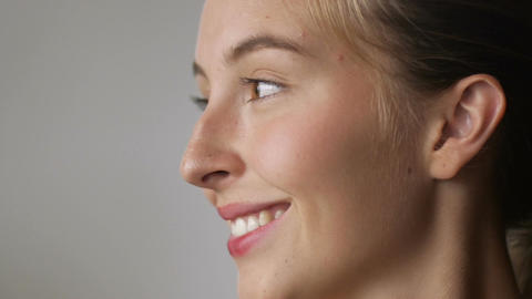 Close up of a woman turning her face to the side and smiling in slow mo with Footage