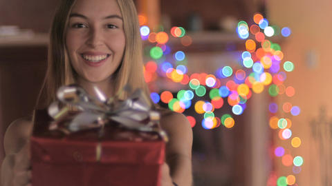 An attractive young woman wearing a Santa hat gives a red wrapped wrapped gift Footage