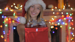 A lovely young woman giving a wrapped Christmas gift and smiling with colored li Footage