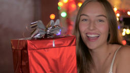 An excited young woman shows off her Christmas present and smiles Footage
