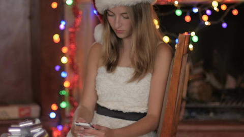A blond women in white holiday dress wearing a red santa hat sits and checks her Footage