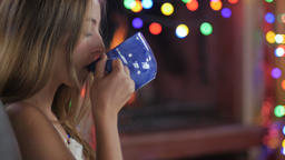 A young woman sips hot tea or chocolate out of a blue mug and then uses her Footage