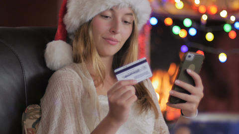A happy attractive young female shopper wearing a Santa hat finishes her online  Footage