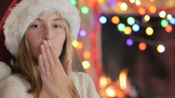 A beautiful young woman in a Santa hat blows a kiss during the holidays in front Footage