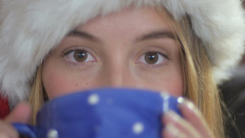 Close up of a young attractive woman in a Santa hat drinking hot tea or hot choc Footage