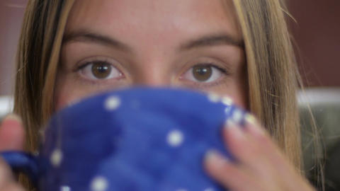 Close up of a very attractive young woman drinking hot coffee, hot chocolate, or Footage