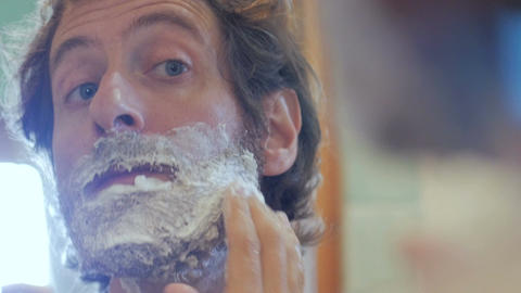 An attractive middle aged man with a full beard applies shaving cream to his fac Footage