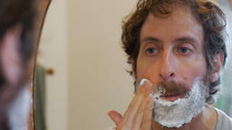 An attractive middle aged man with a full beard applies shaving cream while look Footage
