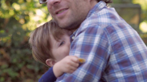 Little blond boy having fun and hugging his 30 something father outside in green Footage