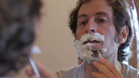 Reflection of middle aged attractive man using a safety razor to shave his beard Footage