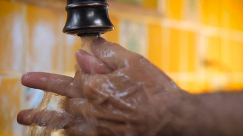 Slow motion closeup of a man washing his hands throughly with soap under running Footage