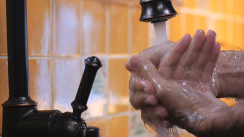 A man washes his hands under a faucet and rinses off the soap in slow mo - close Footage