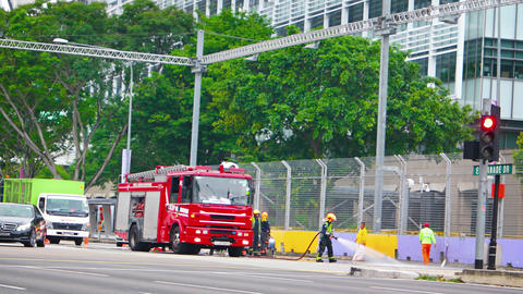 Firefighters using high pressure hoses to clean up roadway in Singapore Footage