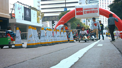 Children riding on toy cars. racing around a temporary track in Hong Kong Live Action