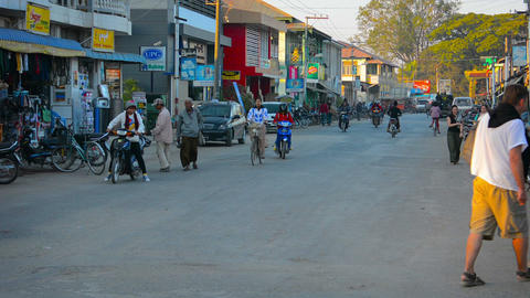 Motorbike. bicycle and people traffic on wide burmese small tourist town road Footage