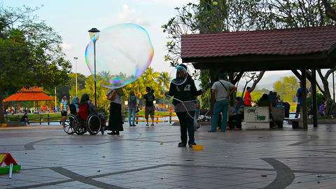 Muslim girl makes huge big soap bubble in big public crowded park Footage