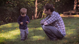 A father wearing glasses and a 2 year old child spending time together outside i Footage
