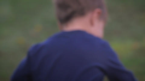 A young little toddler boy in a blue shirt running past the camera and picks up Footage