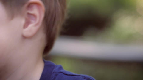 Close up and handheld portrait of a young blond cute healthy boy smiling and pla Footage