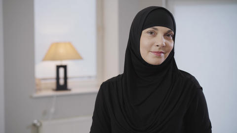 Beautiful Muslim lady in black traditional hijab looking at camera and smiling Live Action