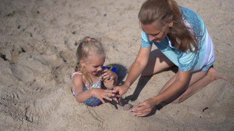 daughter girl buried in sand and her mom playing with sand Live Action