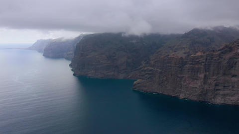 Aerial view of Los Gigantes Cliffs on Tenerife overcast, Canary Islands, Spain Live Action