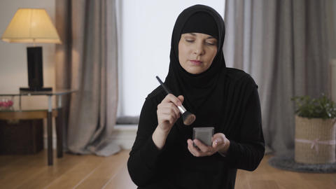 Portrait of attractive Muslim woman applying face powder. Smiling pretty lady in Live Action