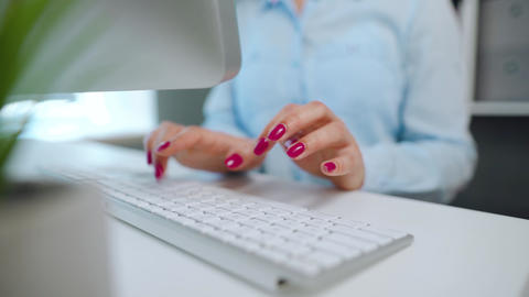 Female hands with bright manicure typing on a computer keyboard Live Action