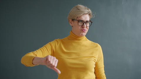 Disappointed adult woman showing thumbs-down gesture shaking head indoors Live Action