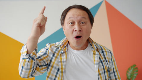 Excited Asian man raising finger showing good idea gesture on colorful Live Action
