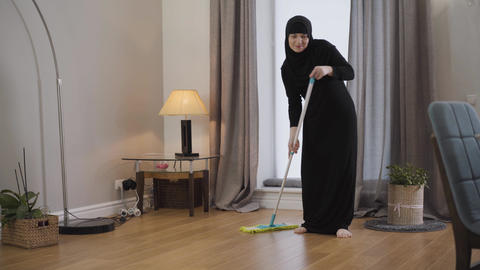 Portrait of young Muslim lady cleaning the floor. Young lady in black hijab Live Action