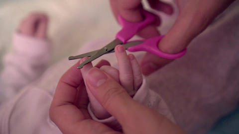 Mom holds the baby fingernails by hand, she holds small special scissors for the Live Action