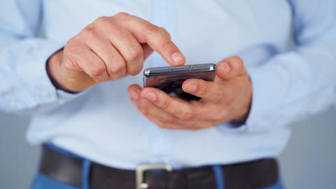 Formally dressed man using smartphone for serfing on internet close-up Live Action
