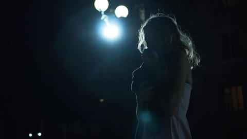 Silhouette of a girl at night in the light of a lantern. Woman feels depressed Live Action
