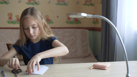 Adorable focused girl sitting at desk and cutting paper sheet Live Action