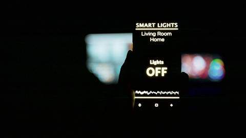 Close up shot of man holding a smartphone in hands with a smart light Live Action