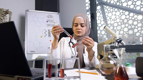 Attractive experienced 35-aged muslim female doctor in hijab comparing chemical Live Action