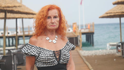 Attractive grandmother relaxing at summer resort near the sea Live Action